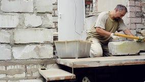 En man bygger en vägg hemma stock video