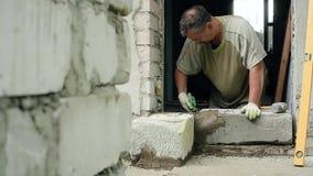 En man bygger en vägg hemma arkivfilmer