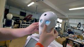 En man döljer det läskiga huvudet för robotar under en vit maskering arkivfilmer