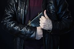 En man döljer en handväska för kvinna` s i hans barm, stölden av en handväska, en svart bakgrund, stöld av påsar arkivbild