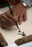 En man drar en kinesisk kalligrafi i en gata av Hanoi (Vietnam) Royaltyfri Bild