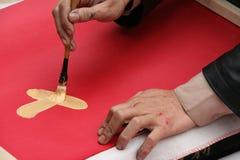 En man drar en kinesisk kalligrafi (Vietnam) arkivfoto
