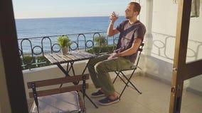 En man dricker vin på en balkong mot havet stock video