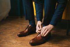 En man eller en brudgum i en blå dräkt binder upp skosnöre på bruna brogues för läderskor på en träparkettbakgrund Royaltyfri Foto