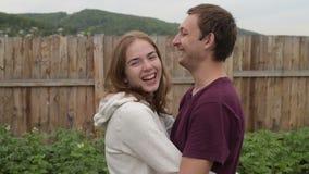 En man en vrouw die koesteren lachen stock videobeelden