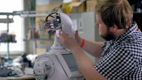 En man fäster skruvar på ett robothuvudskal arkivfilmer