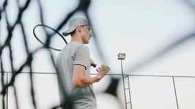 En man för en lek av tennis, trimmar in i leken, kastar bollen arkivfilmer