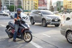 En man för leveransmopedtaxi befriar en motorisk cirkulering på upptaget s royaltyfria bilder