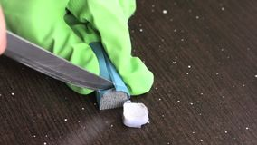 En man förbereder ettdel epoxylim Snitt med en kniv ett jämbördigt belopp av två delar för blandning Kall svetsande teknolog stock video