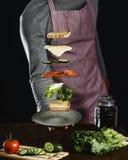 En man förbereder ingredienserna för en läcker vegetarisk smörgås arkivfoto