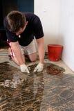 En man förlägger en keramisk tegelplatta under tryck över ett lim i rum av brun färg royaltyfria bilder