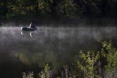En man fiskar på floden dimmig morgonsommar royaltyfri bild