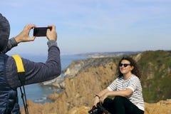 En man fotograferar en flicka med en kamera på telefonen royaltyfri bild