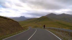En man fotvandrar vid vägen i Kaukasus berg Hake-fotvandra 4K UHD arkivfilmer