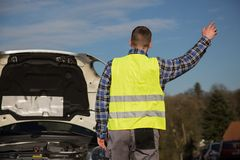 En man frågar för hjälp på vägen nära hennes brutna bil Arkivfoto