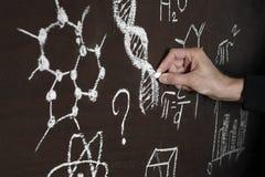 En man fr?n m?rker skriver DNAkod och formler p? en svart tavla royaltyfri fotografi