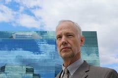 En man framme av en blå kontorsbyggnad arkivbild