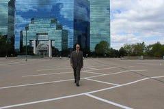 En man framme av en kontorsbyggnad arkivbild