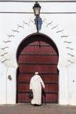 En man framme av moskén i Marrakech, Marocko Arkivfoto