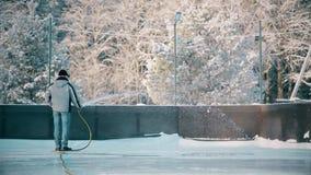 En man fyller upp isbanan med vatten från en slang lager videofilmer