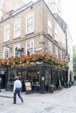 En man går förbi pub för Ye Olde Watling på hörnet av den Watling gatan och pilbågegränden, London, England, Förenade kungariket arkivbilder