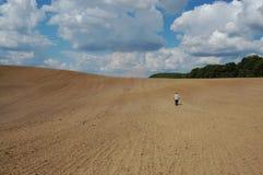 En man går i det bruna fältet i avståndet Arkivfoto