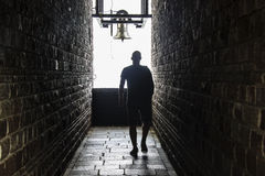 En man går in i en mörk tunnel, men shower för ett ljus på slutet Arkivbild