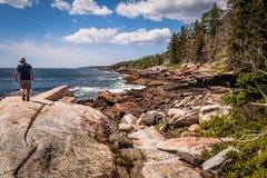 En man går på den stora stenblocket som omges av stenig shoreline i Bristol, Maine, på 7/03/17 Royaltyfria Foton