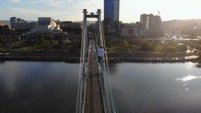 En man går på ett rep som sträcks mellan servicen av bron på hög höjd arkivfilmer