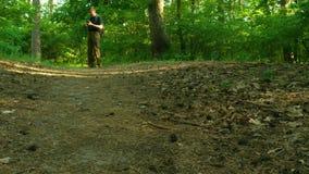 En man går till och med skogen och söker efter en väg med hjälpen av en navigatör Han går in mot kameran Fotvandra kängaslut-u lager videofilmer