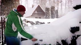En man gör klar snön av bilen i morgonen efter ett snöfall stock video