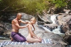 En man gör en massage för en kvinna i naturen bredvid en wat royaltyfri bild