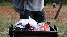 En man gör ren avfall i en allmänhet parkerar upp Begreppet av att att bry sig för miljön och att att bry sig för miljön Hösten p stock video