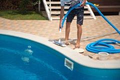 En man gör ren en simbassäng med en slang med en borste, personal Arkivfoton