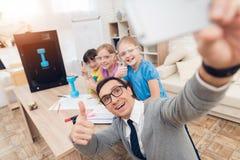 En man gör en selfie med barnen i klassrumet Arkivbild