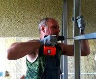 En man gör en vägg av drywall arkivbilder