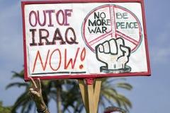 En man ger fredtecknet och rymmer ett tecken som nu säger, ut ur Irak på en marsch för anti--Irak krigprotest i Santa Barbara, Ka arkivfoto