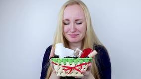 En man ger en härlig flicka en gåva - en korg med skönhetsmedel och hygienprodukter Angenäm överraskning för födelsedagen, valent arkivfilmer