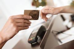 En man ger en kvinna en kontokort för betalning Mot bakgrunden står träräknaren som står på terminalen royaltyfri bild