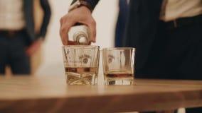 En man häller alkohol från en flaska in i ett exponeringsglas Trevligt ultrarapidplan stor deltagare lager videofilmer