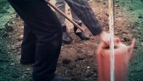 En man häller vatten på jordningen arkivfilmer