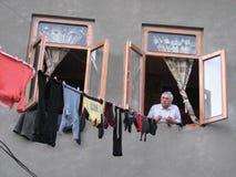 En man hänger hans tvätteri ut ur ett fönster av Kutaisi, Georgia Royaltyfria Foton