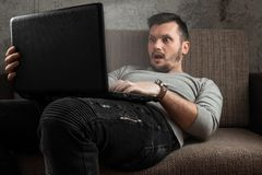 En man h?ller ?gonen p? en vuxen video p? en b?rbar dator, medan sitta p? soffan Begreppet av pornografi, masturbation, manliga b royaltyfri bild