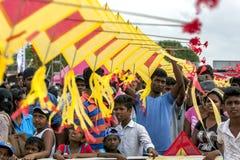 En man hjälper att rymma en japansk drake ovanför en folkmassa av folk på Negombo för att sätta på land i Sri Lanka Royaltyfri Fotografi