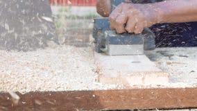 En man hyvlar en planka med en elektrisk nivå, trächiper stock video