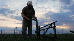 En man i ålder klipper av en metallvinkelmolar på solnedgången Härlig himmel bak arbetaren arkivfilmer