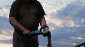 En man i ålder klipper av en metallvinkelmolar på solnedgången Härlig himmel bak arbetaren stock video