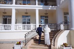 En man i en affärsdräkt rymmer en flicka i en bröllopsklänning, och en kappa vid handen, hjälper henne att klättra trappan Barn arkivbild
