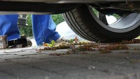 En man i arbetsbyxa byter ut ett bilhjul lager videofilmer