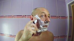 En man i badrummet rakar skäggstubben runt om hans tempel med en rakkniv arkivfilmer